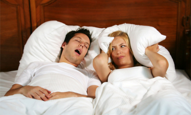Couple in bed while the woman is trying to sleep and the man is snoring. Shutterstock